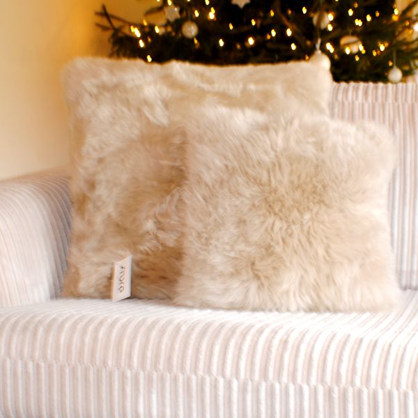 two cream fur cushions on a cream sofa