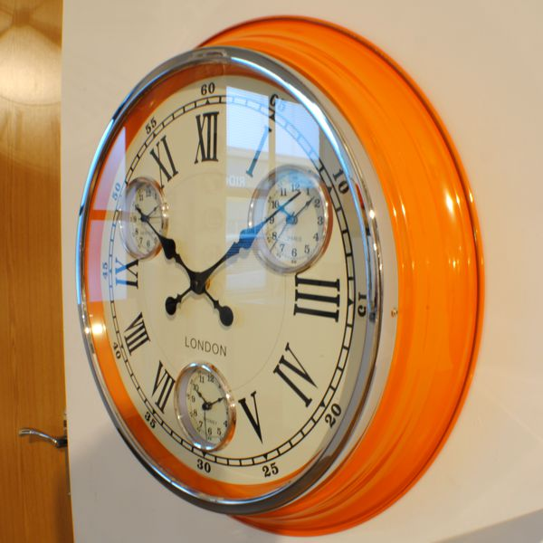 large round wall clock with orange case, cream face, black roman numerals and 3 additional dials for different timezones