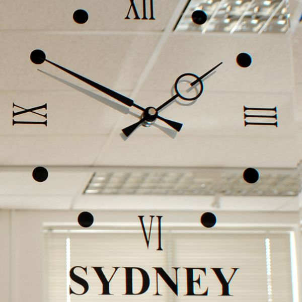 face on mirror wall clock with three time zones