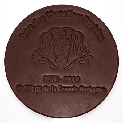a brown round leather coaster with embossed design