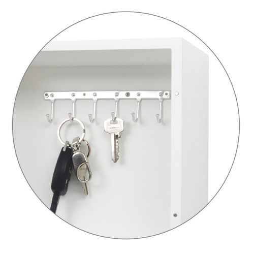 cabinet behind wall clock with keys hanging on hooks