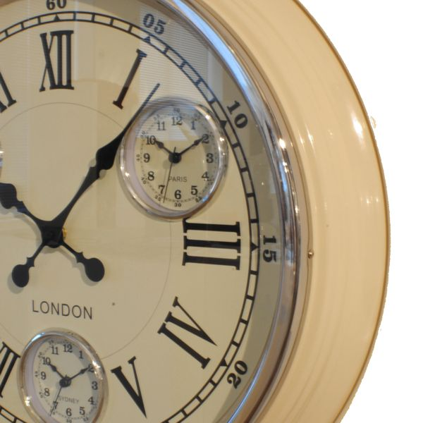 close up of timezone wall clock with cream metal case, cream dial with black roman numerals and 3 additional dials
