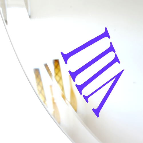 close up of purple roman numeral on bevelled mirror wall clock