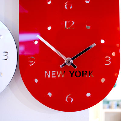 close up of the clock face of a red acrylic timezone wall clock