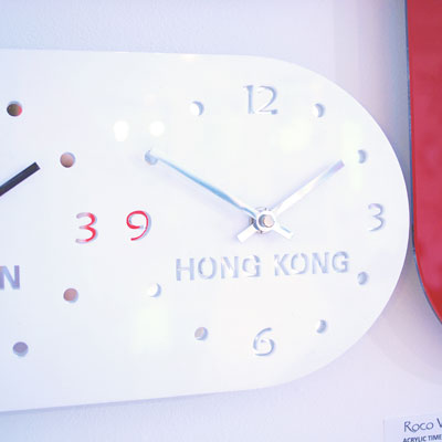 close up of one end of a white acrylic timezone clock showing silver hands and digits