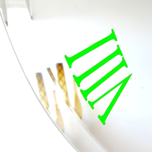 close up of lime green roman numeral on bevelled mirror wall clock