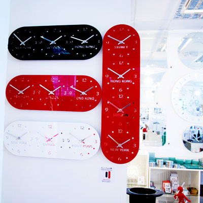 3 horizontal timezone wall clocks in black, white and red next to a vertical red timezone clock