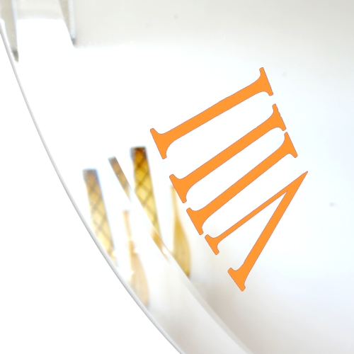 close up of orange roman numeral on bevelled mirror wall clock