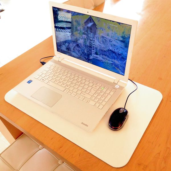 lap top on large white leather desk mat on light wood table
