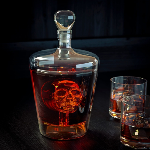 glass decanter with embossed skull on the front and filled with orange liquid