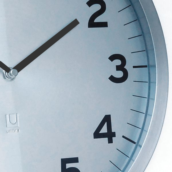 close up office clock with custom time zone sign silver grey dial