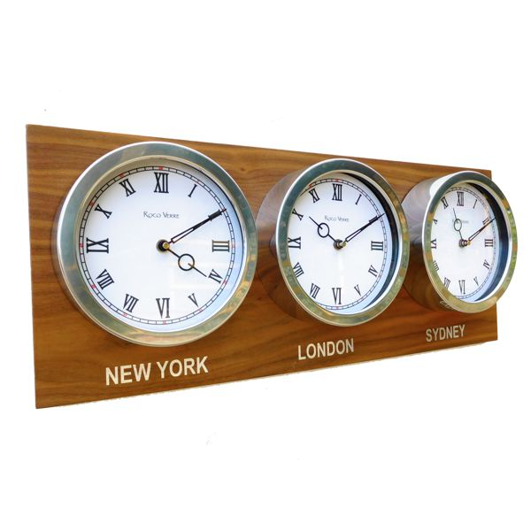 side view of three white timezone clocks on walnut back board