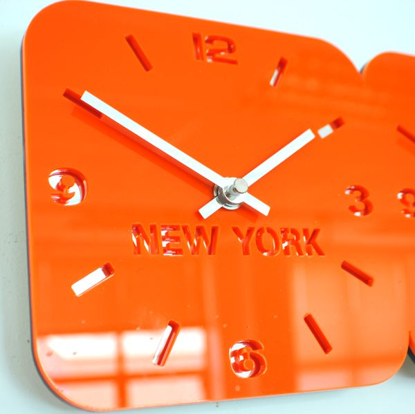 close up of gloss orange triple dial world timezone wall clock