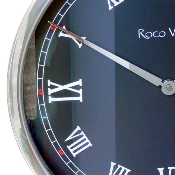 round wall clock with black dial, white roman numerals and metal surround