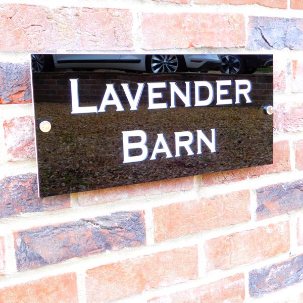 white and gloss black house sign on brick wall