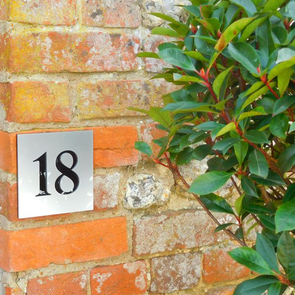 silver number house sign on brick wall