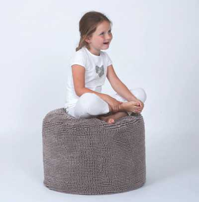 young girl sitting on ZicZac Spiky Soft Luxury Pouffes in taupe colour