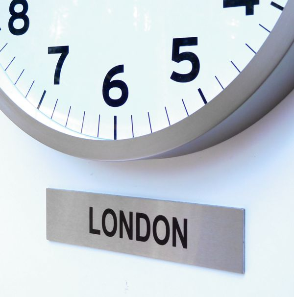 close up offcie clock with custom timezone sign