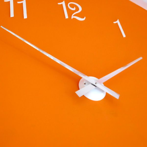close up Roco Verre white Gloss Luna Hand Clock white french numbers on orange wall
