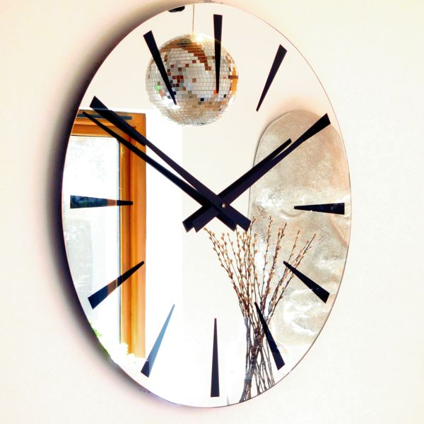round mirror wall clock with black chevron digits and black hands