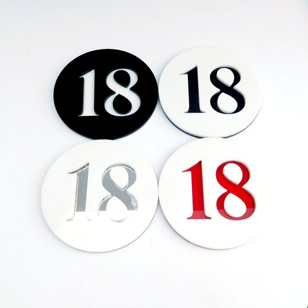 a number of round number door house numbers in various colours