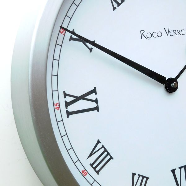 round wall clock with white dial, black roman numerals, black hands and metal case