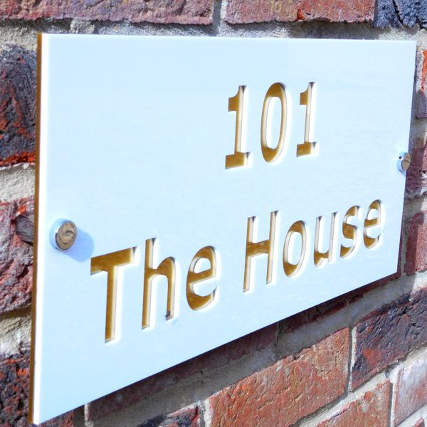 gloss white and brass house sign on brick wall