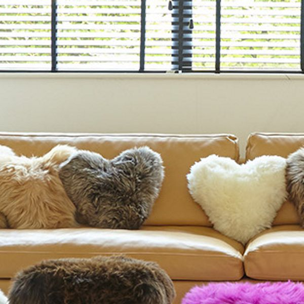 three heart shape wool cushions on a biege sofa