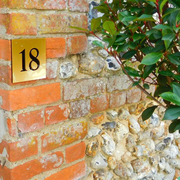 brass and black gloss house number and door number sign