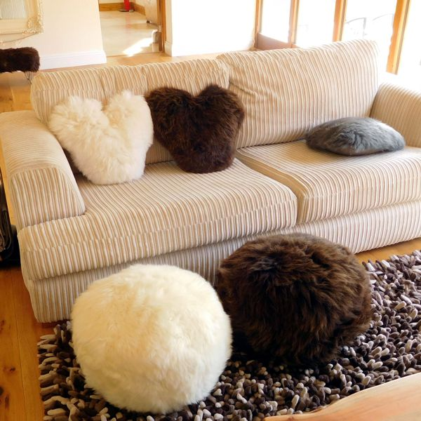 lounge room setting with cream sofa, brown rug, wool heart shape cushions and wool puffes