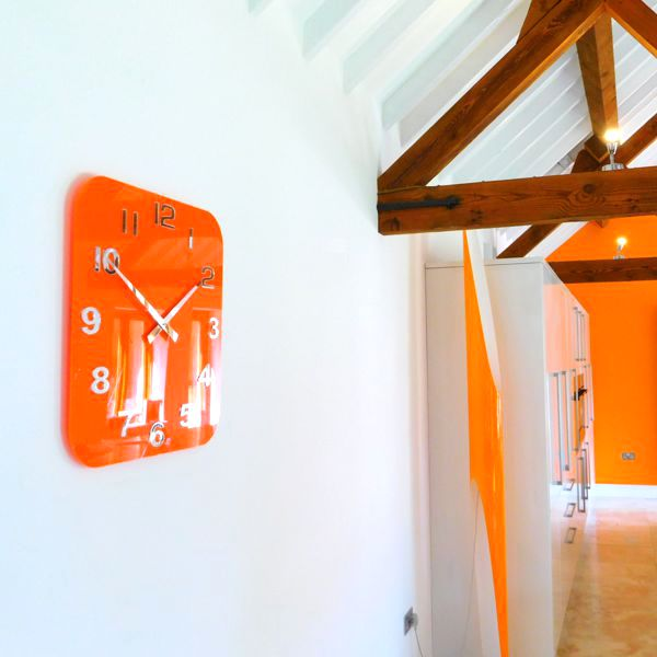 large orange retro style gloss acrylic clock on a kitchen wall
